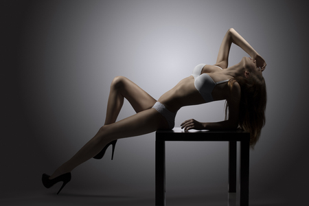 hot backlight portrait of alluring girl posing on small table with sexy white lingerie showing her perfect body  photo