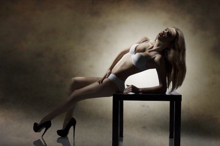glamour backlight shoot of seductive brunette girl in sensual pose on small table showing her perfect silhouette with white lingerie  photo