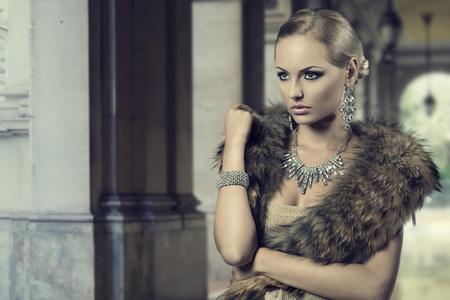 mode portret van luxe blonde meisje poseren met elegante kapsel, bont sjaal en kostbare glanzende juwelen Stockfoto