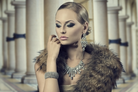 close-up mode portret van sensuele blonde meisje met luxe stijl, poseren met een elegante kapsel en make-up en het dragen van bont sjaal en rijke glanzende juwelen Stockfoto