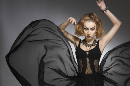 strange: fashion portrait of pretty girl with bizarre gothic style, make-up and accessories and big flying skirt
