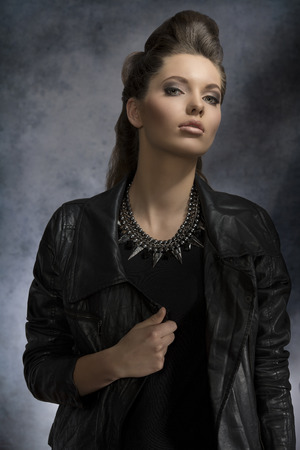 fashion portrait of pretty brunette girl with dark style and modern hair-style wearing rock necklace and leather jacket  photo