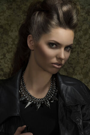 close-up portrait of sexy young brunette with gothic rock style, posing with brown modern hair-style, leather jacket and rock necklace. Looking in camera  photo