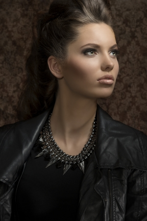 fashion close-up shoot of sensual young girl with modern gothic style and long brown hair wearing leather jacket and rock necklace  photo