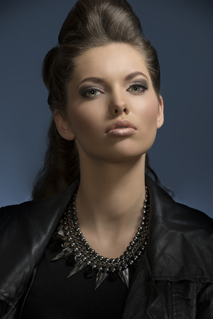 pretty girl posing in close-up fashion shoot with dark rock look and cute brown hair-style, wearing leather jacket and modern necklace looking in camera  photo