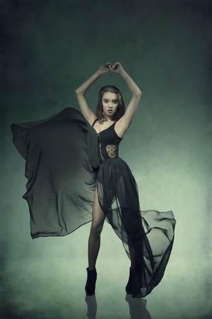 full length portrait of young woman with dark fashion dress with fluttering transparent skirt, natural hair-style looking in camera  photo