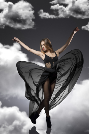 transparent dress: sensual young female pose in fashion portrait and wearing sexy transparent dark dress with fluttering veil skirt  Stock Photo