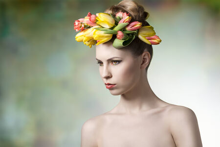 sensual young girl posing in spring portrait with floral wreath on her head, naked shoulders and fresh colorful make-up  photo