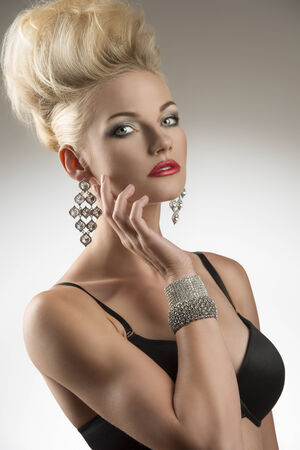 portrait of sexy blonde girl with black bra, modern creative hair-style and glossy jewelleries  photo