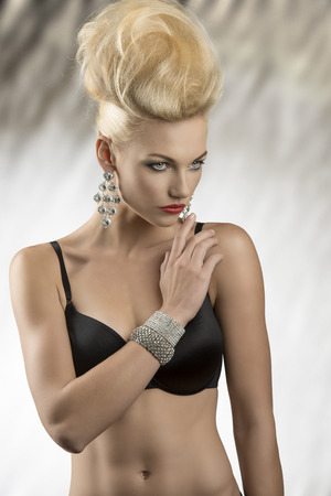 portrait of charming blonde woman with fashion  hairdo and glossy jewelleries posing in lingerie. Wearing black bra photo