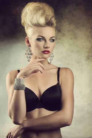 sexy portrait of charming young girl posing with aristocratic expression, creative hair-style and lingerie. Wearing black bra and glossy jewelleries  photo