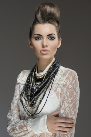 fashion portrait of sexy brunette with elegant hair-style and a lot of necklaces. Wearing  white lace shirt and looking in camera  photo