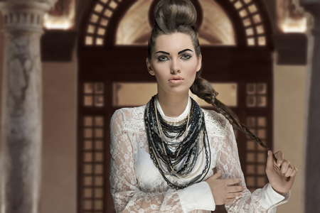 hairdo: portrait of sensual young brunette woman with creative fashion style and cute hairdo and make-up. Wearing white lace shirt and a lot of necklaces