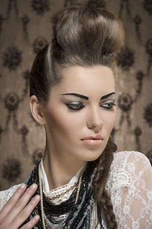 close-up fashion portrait of charming female with creative look, cute brunette hair-style and strong make-up. Wearing white lace shirt and a lot of necklaces photo
