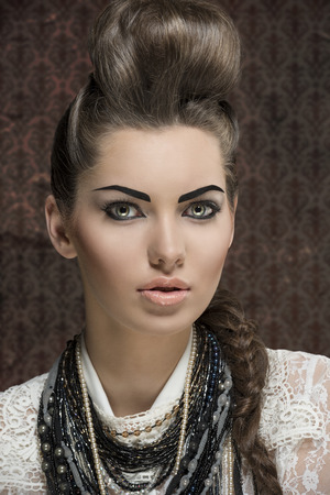 close-up shoot of fashion creative brunette girl posing with elegant hair-style and strong make-up,  white lace shirt and a lot of necklaces  photo