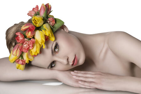close-up portrait of pretty blonde girl with bared shoulders, lying on a table wearing spring floral garland and looking in camera  photo