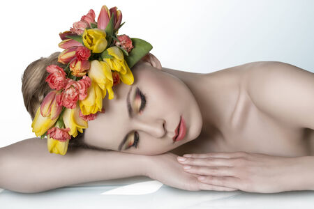 portrait of sensual blonde woman with colorful make-up, fresh skin, bared shoulders and spring floral garland on the head. Lying on table  photo