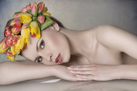 close-up portrait of sexy blonde girl with spring look posing lying on table with bared shoulders, colorful make-up and floral garland  photo