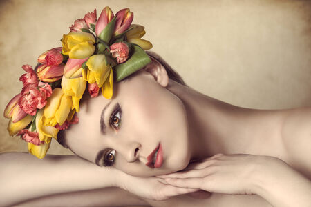 close-up portrait of lovely young girl with spring style, floral wreath on her head and colorful make-up. Lying on her hands with calm expression   photo
