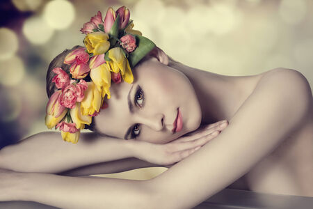 lovely beauty girl with spring floral wreath, colorful make-up, fresh skin and naked shoulders lying on a table and looking in camera with calm expression  photo