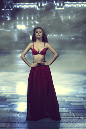 fashion shoot of very sexy girl with flying hair, red bra and long veil transparent skirt  photo