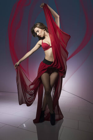 sexy woman in dancer pose and flying hair wearing red lingerie and long fluttering skirt  photo