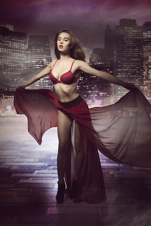 amazing fashion portrait of cute brunette girl with flying hair, red bra and long fluttering skirt. Posing with romantic expression  photo