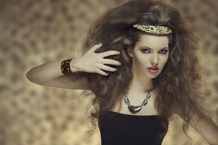 fashion portrait of cute brunette girl with curly hair-style, cute make-up and leopard accessories  photo