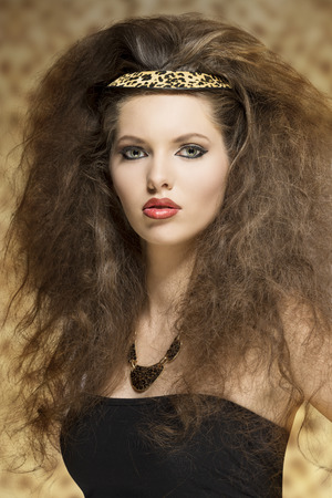 cute young girl with long curly hair-style and leopard accessory posing with pretty make-up and looking in camera  photo