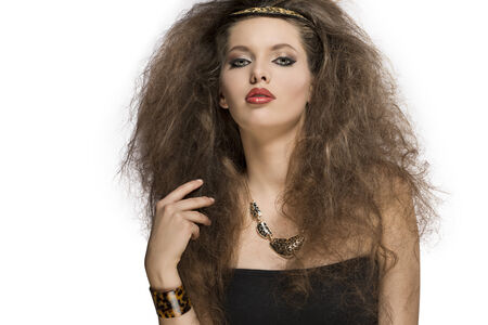 wild hair: sexy young woman posing in fashion shoot with wild style, brown curly hair-style, leopard accessories and necklace and cute make-up. looking in camera with charming expression
