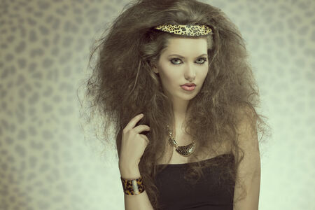 charming fashion brunette lady with long curly brown hair-style, pretty make-up and leopard accessories and necklace.  photo