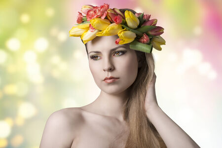 portrait of beauty young woman with long blonde hair, fresh skin, floral garland on her head and colorful make-up. bared shoulders and romantic eyes  photo