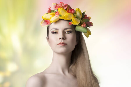 spring concept portrait of sexy woman with bared shoulders, long smooth hair and colorful make-up, wearing floral wreath on her head. Fresh style  photo