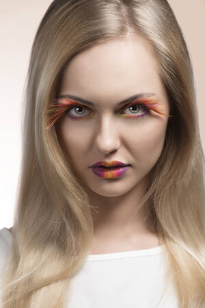 smooth hair: beauty close-up portrait of pretty blonde girl with long smooth hair, colorful and feathered make-up wearing white dress looking in camera  Stock Photo