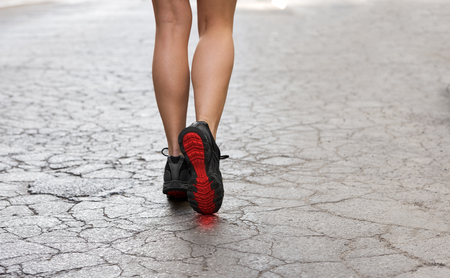 foots: back shot of young lady with fitness shoes in act to walking ,running on a broken fashion road
