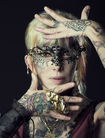 tattoo face: Woman , not young , with tattoo on face and arm, ready for party carnival , with black fashion mask