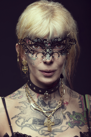 arm tattoo: Woman , not young , with tattoo on face and arm, ready for party carnival , with black fashion mask