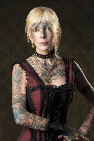 carnival portrait of tattoo woman with red gothic costume and gold ornaments