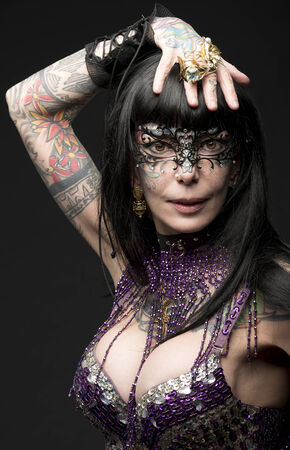 sexy adult female posing with bizarre carnival style and tattoos, glitter bra and baroque mask  Stock Photo