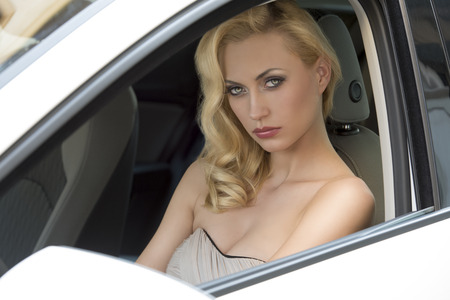 sensual blonde girl with elegant dress and cute make-up sitting in a white car and looking in camera  Stock Photo - 26362346