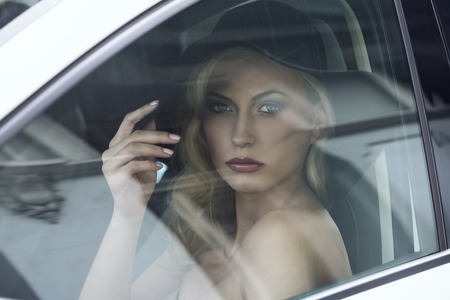 close-up portrait of fashion girl posing in white car with black hat, cute make-up, blonde hair and aristocratic style Stock Photo - 26362347