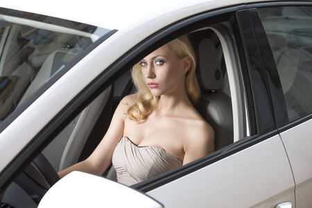 sexy blonde woman with elegant style sitting in a white car  photo