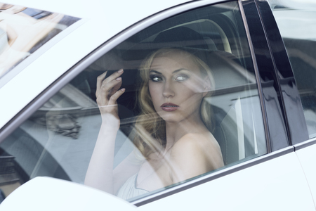fashion portrait of glamour blonde woman with elegant style and black hat  sitting in a white car Stock Photo - 26362352