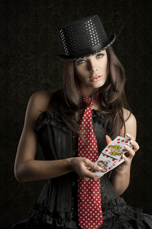 sexy woman with burlesque dress playing with poker cards and looking in camera  Standard-Bild