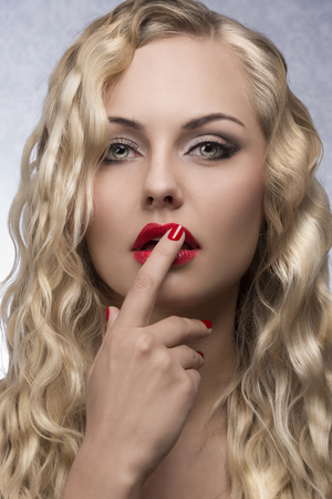 beauty close-up portrait of pretty blonde girl with wavy shiny hair, red lipstick and nail polish. Sensual pose   photo