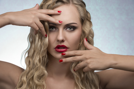 beauty portrait of sexy female with luxury red lipstick, nail polish and blonde wavy shiny hair-style  photo