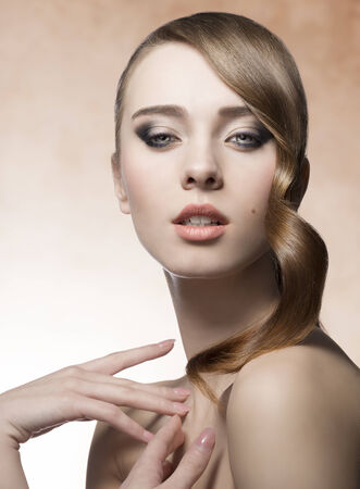 hair tuft: beauty woman with perfect skin, cute make-up and shiny brown hair-style with wavy tuft near the visage  Stock Photo