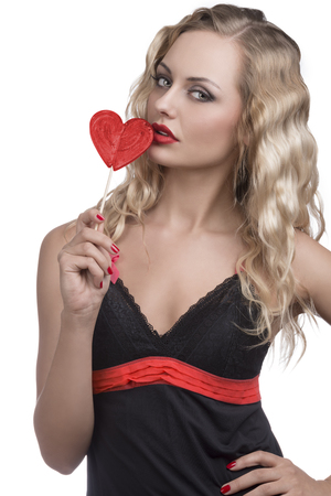 sexy blonde woman with black dress, long wavy hair and red lollipop  photo