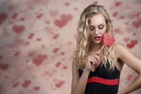 cute young woman with long wavy blonde hair and sexy dress taking heart shaped lollipop in the hand  photo
