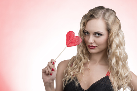 lovely young girl with wavy blonde hair-style and sexy dress posing with red heart shaped lollipop in the hand  photo